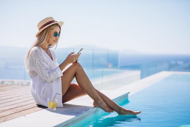 Jovem mulher em férias na piscina usando telefone