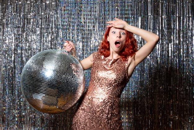 Jovem mulher em festa com bola de discoteca em cortinas brilhantes