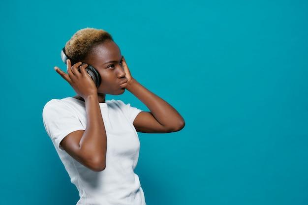 Jovem mulher em fones de ouvido bluetooth, curtindo música