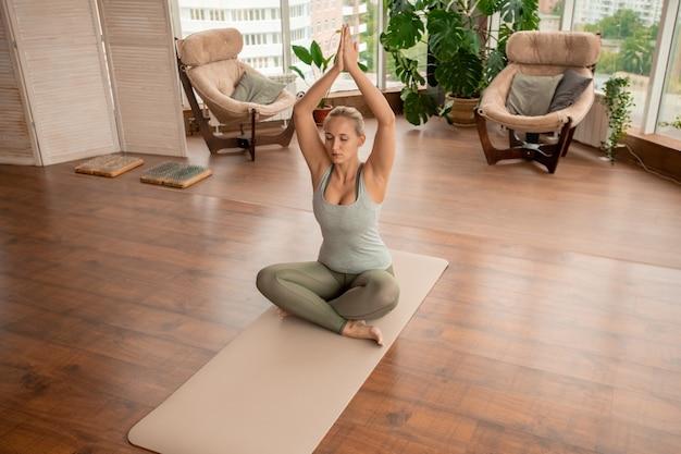 Jovem mulher em forma, ativa, mantendo o equilíbrio com as mãos postas sobre a cabeça enquanto se senta na posição de lótus durante o exercício de relaxamento