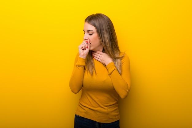 Jovem mulher em fundo amarelo está sofrendo com tosse e se sentindo mal
