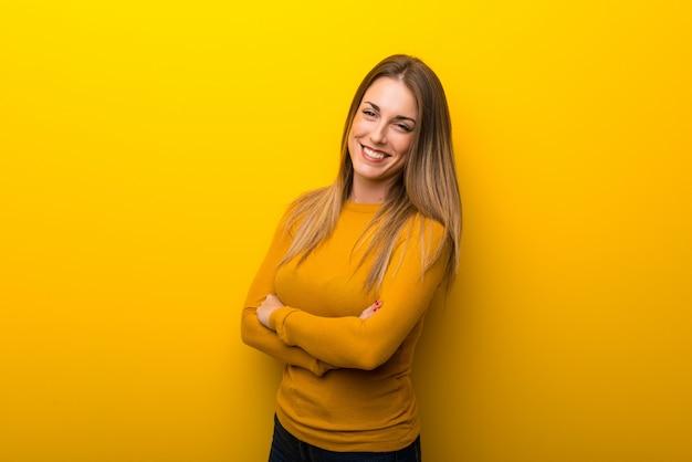 Jovem mulher em fundo amarelo, mantendo os braços cruzados em posição frontal