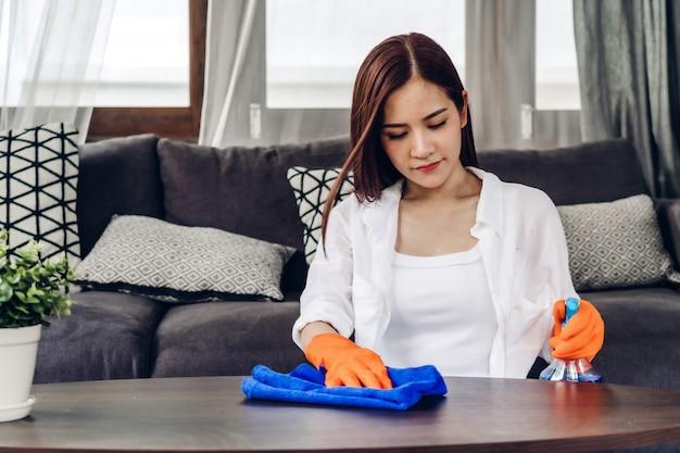 Jovem mulher em luvas de proteção usando spray de limpeza