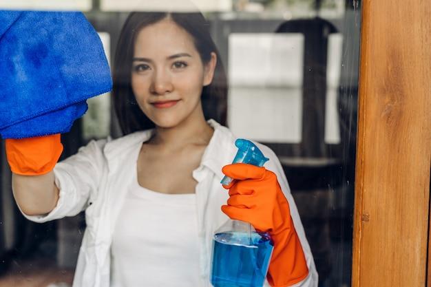 Jovem mulher em luvas de proteção usando um spray e um pano durante a limpeza da janela na sala de estar em casa. conceito de limpeza doméstica e doméstica