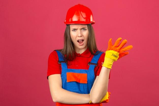 Jovem mulher em luvas de uniforme de construção e capacete de segurança vermelho, fazendo o gesto de questionamento, sentindo-se confuso e indignado em fundo rosa escuro