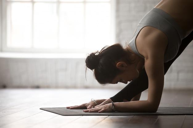Jovem mulher em one sided fold pose, estúdio branco
