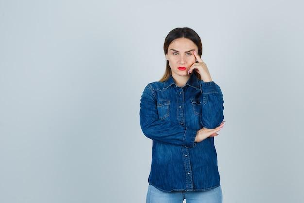 Jovem mulher em pé pensando em pose de camisa jeans e jeans e olhando pensativa