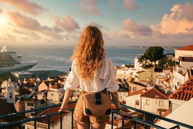 Jovem mulher em pé sobre uma plataforma cercada por cercas e observando lisboa durante o dia em portugal