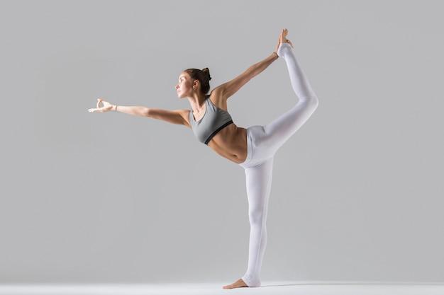 Jovem mulher em pose de natarajasana, fundo de estúdio cinza