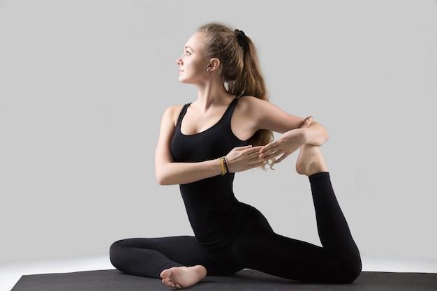 Jovem mulher em pose de pombo-rei com uma perna, estúdio cinza