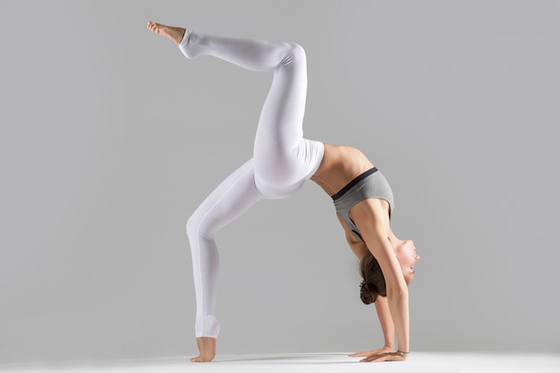 Jovem mulher em pose de roda de uma perna, estúdio cinza