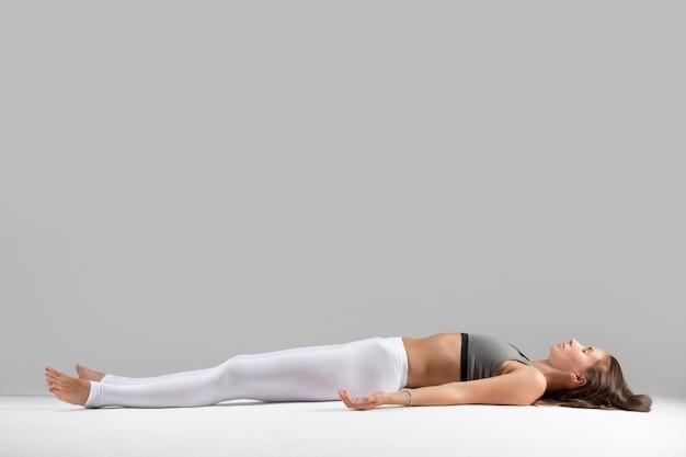 Jovem mulher em pose de savasana, fundo de estúdio cinza