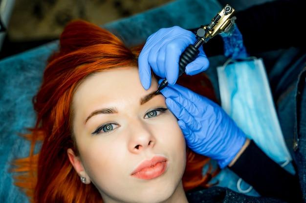 Jovem mulher em processo de maquiagem permanente sobrancelha no salão de tatuagem.