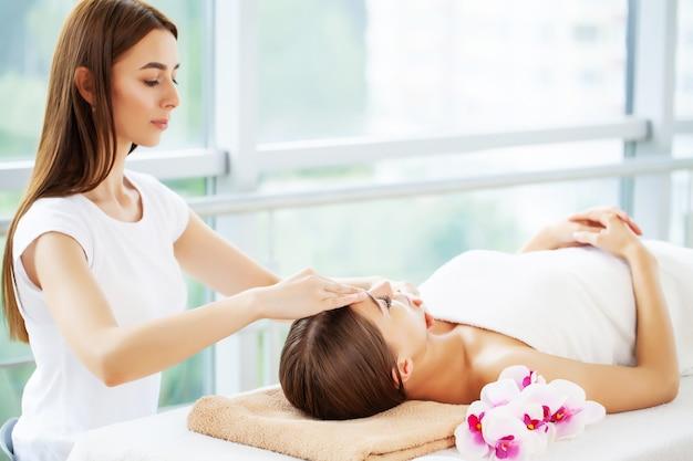 Jovem mulher em rejuvenescer a massagem facial no estúdio de beleza