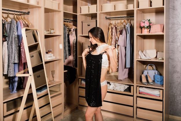 Jovem mulher em roupa interior pensando que vestido vestir na frente das roupas no guarda-roupa.
