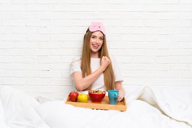Jovem mulher em roupão com café da manhã comemorando uma vitória
