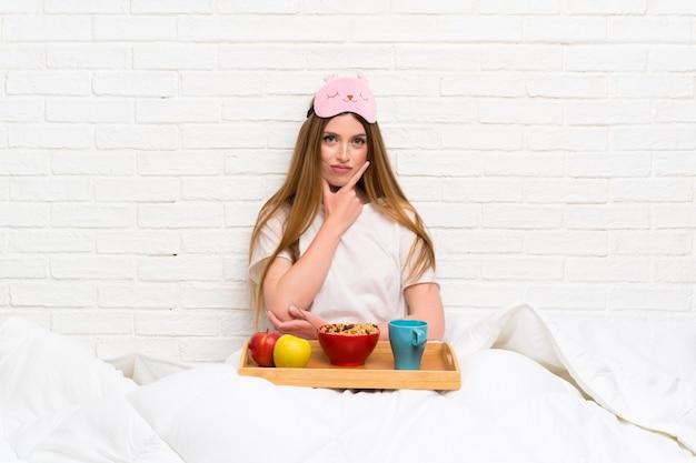 Jovem mulher em roupão com café da manhã pensando uma idéia