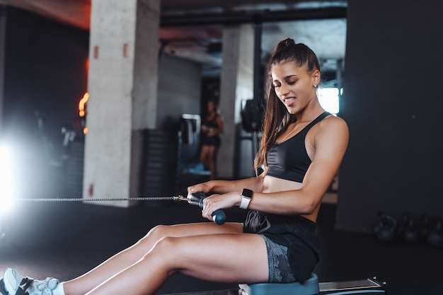 Jovem mulher em roupas esportivas no ginásio, treinando e puxando pesos na máquina de fileira de cabos sentados.