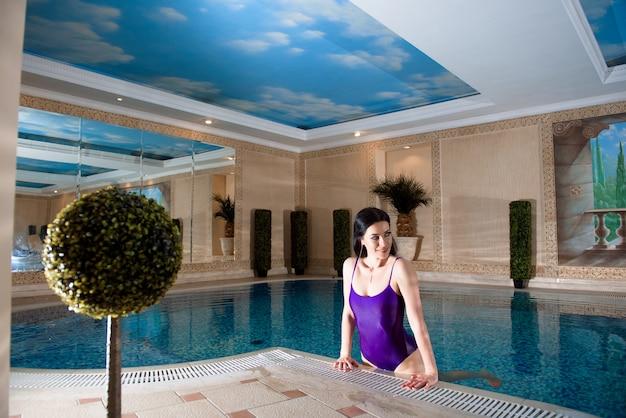 Jovem mulher em spa relaxante à beira da piscina