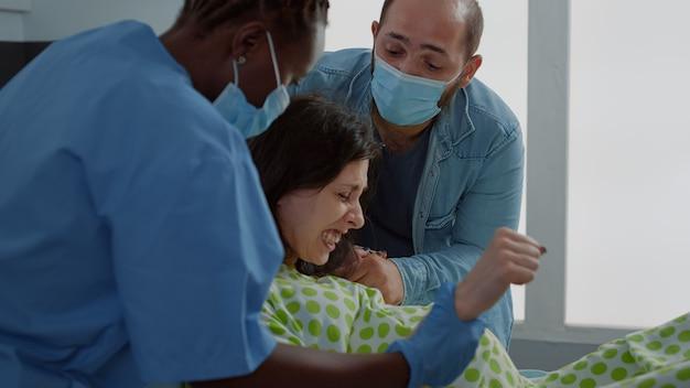 Jovem mulher em trabalho de parto dando à luz um bebê na enfermaria do hospital