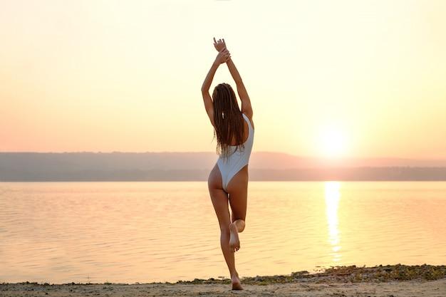 Jovem mulher em traje de banho cordas fica na praia ao nascer do sol