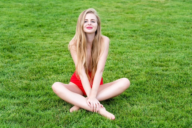 Jovem mulher em traje de banho vermelho, banhos de sol na grama. lazer de verão, ao ar livre no parque em resort de luxo.