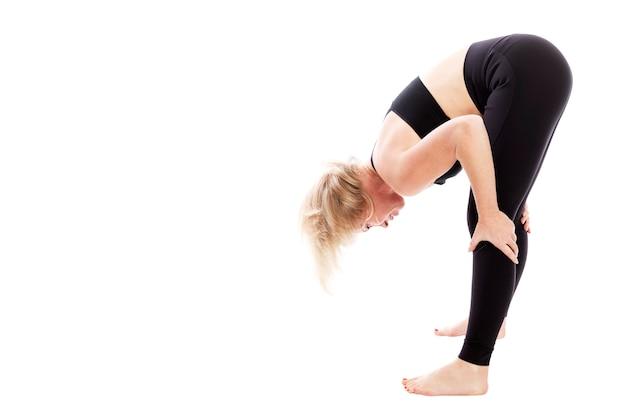 Jovem mulher em traje de fitness preto fazendo alongamento em pé. isolado sobre o fundo branco espaço para texto.
