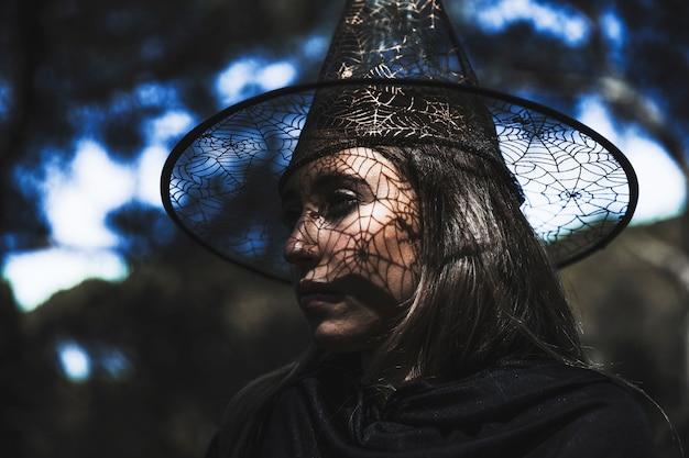 Jovem mulher em traje de mago com metade virou a cabeça olhando para longe