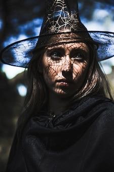 Jovem mulher em traje de mago olhando para longe na floresta