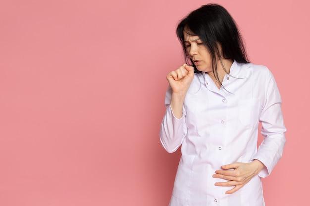 Jovem mulher em traje médico branco tossindo em rosa
