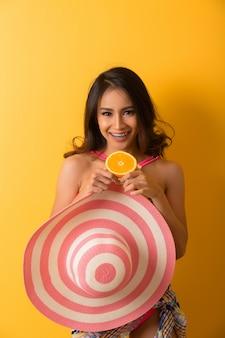 Jovem mulher em trajes de banho isolado sobre o amarelo