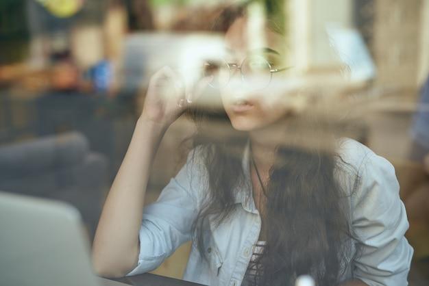 Jovem mulher em um café bebe chá e trabalha, freelancer