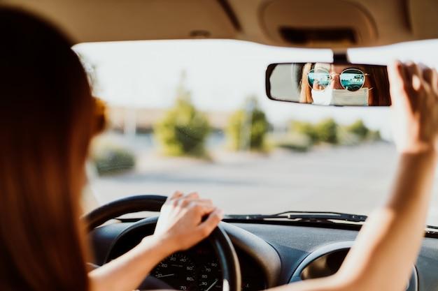Jovem mulher em um carro usando máscara protetora