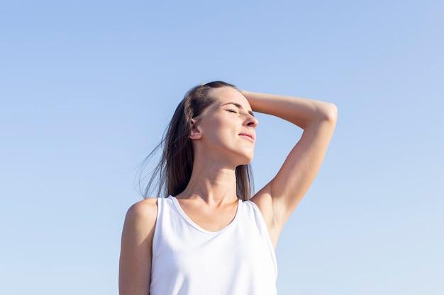 Jovem mulher em um dia ensolarado, contra o pano de fundo de um céu azul claro.