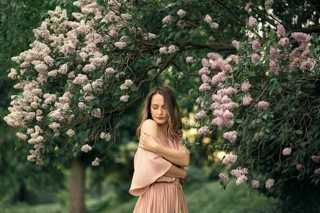 Jovem mulher em um lindo vestido está de pé perto de um arbusto lilás