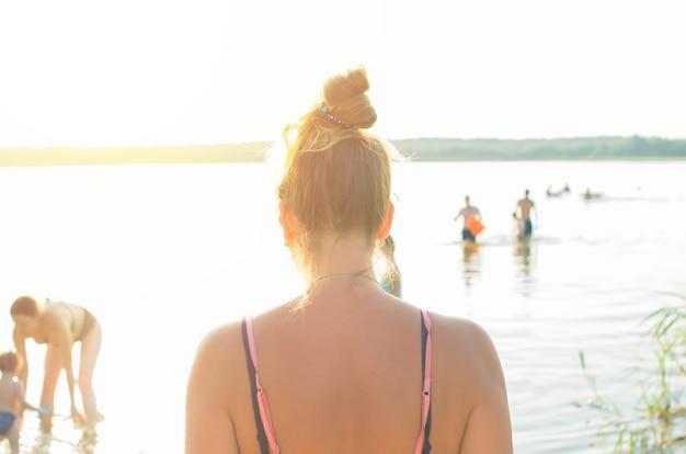 Jovem mulher em um maiô em pé na praia à beira-mar ao pôr do sol ou nascer do sol, vista de trás. menina olhando para o horizonte, pessoas flutuantes de fundo desfocado.