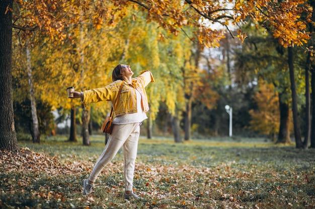 Jovem mulher em um parque outono bebendo café