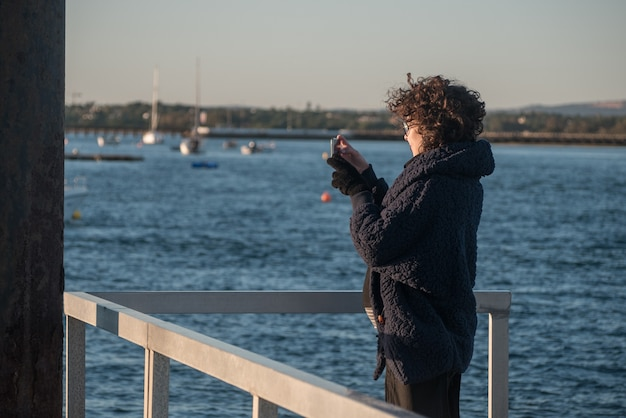 Jovem mulher em um píer, tirando fotos do celular.