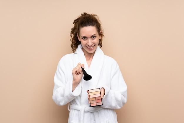 Jovem mulher em um roupão de banho com paleta de maquiagem sobre isolado