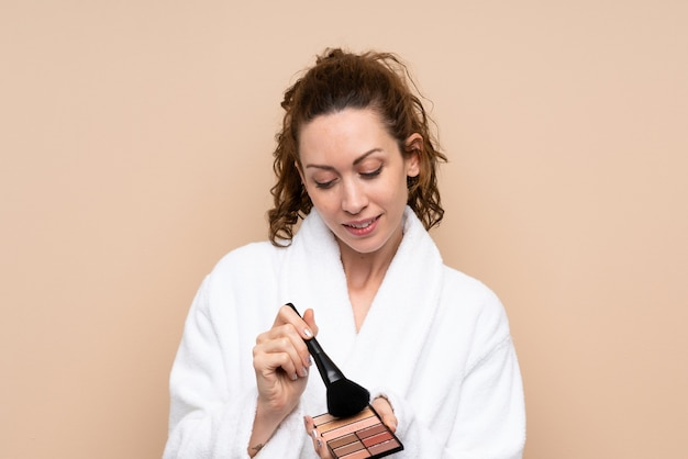 Jovem mulher em um roupão de banho com paleta de maquiagem sobre parede isolada