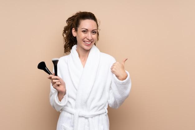 Jovem mulher em um roupão segurando os pincéis de maquiagem apontando para o lado para apresentar um produto