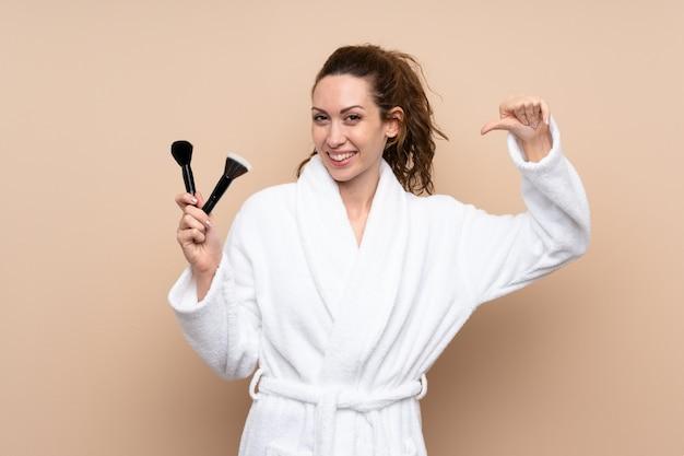 Jovem mulher em um roupão segurando os pincéis de maquiagem orgulhoso e satisfeito