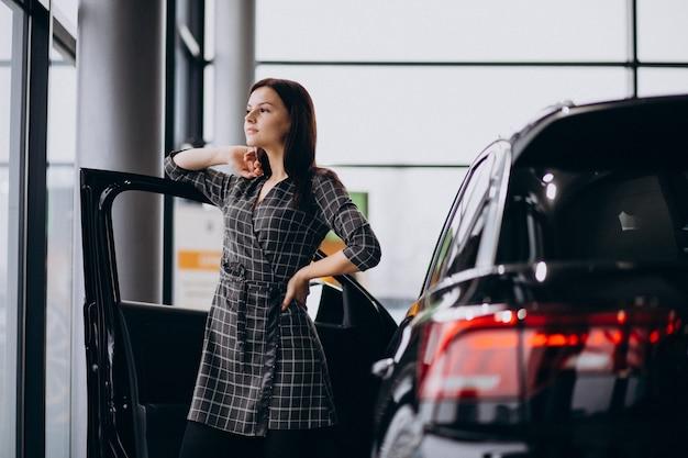 Jovem mulher em um showroom de carro, escolhendo um carro