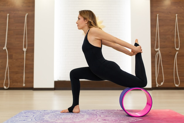 Jovem mulher em um sportswear yoga exercícios com uma roda de ioga no ginásio. estilo de vida de alongamento e bem-estar