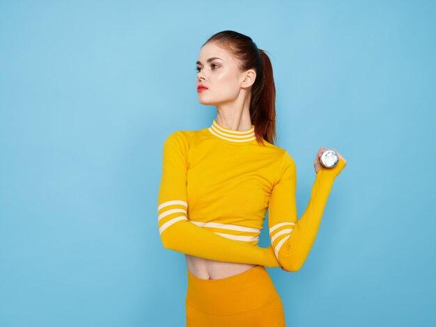 Jovem mulher em um terno de esportes amarelo brilhante com halteres faz esportes em um espaço azul