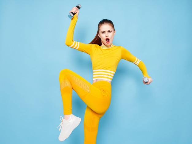 Jovem mulher em um terno de esportes amarelo brilhante com halteres faz esportes em uma superfície azul