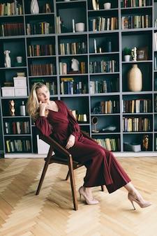Jovem mulher em um terno vermelho na biblioteca. menina no quarto com livros