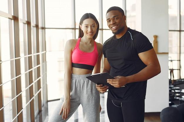 Jovem mulher em um top rosa em pé com um treinador