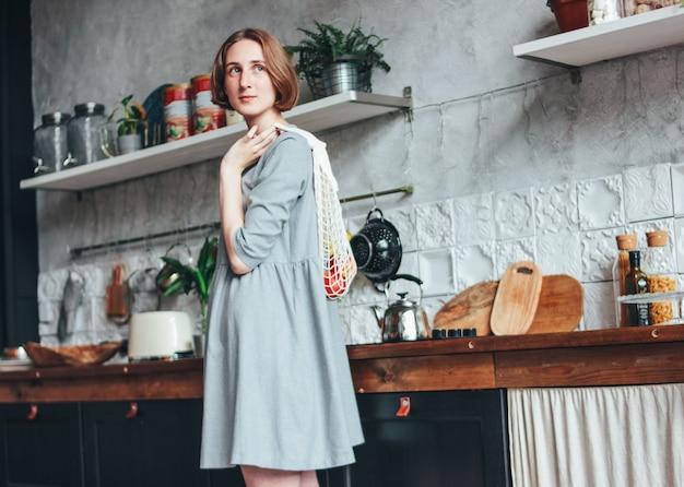 Jovem mulher em um vestido cinza com saco de pano de malha, comprador de saco de cordas na cozinha