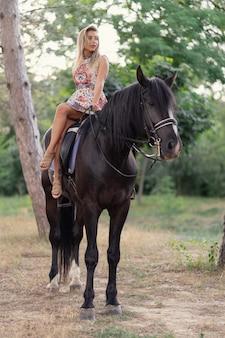 Jovem mulher em um vestido colorido brilhante, montando um cavalo preto